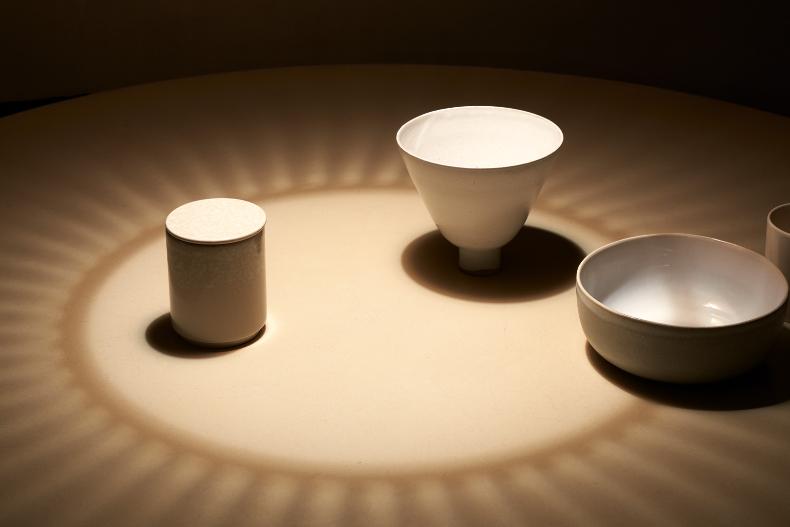 There are beige bowls on the table and a shadow surrounds them.