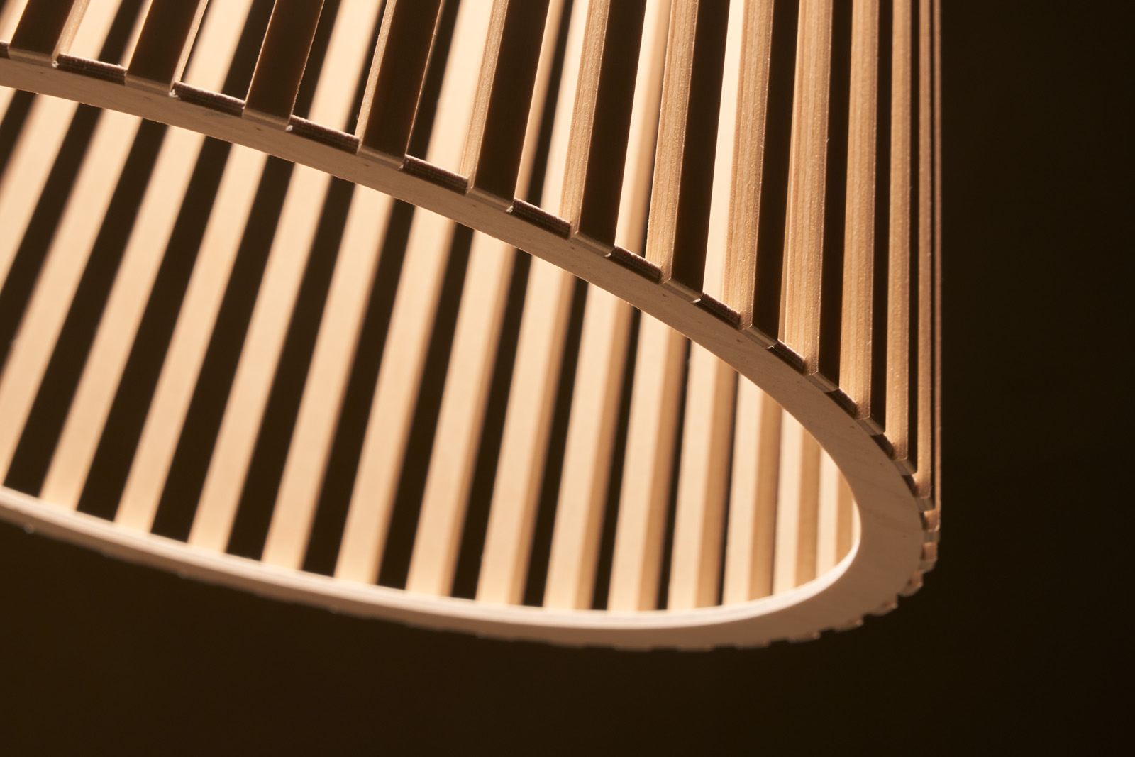 Lampshade's delicate wooden slats turn into intriguing figures as they filter light
